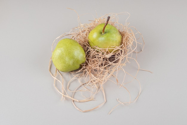 Delicious pears on a small straw pile on marble