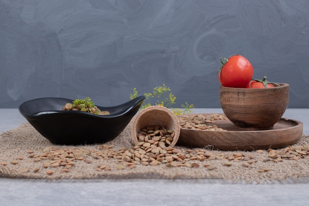 Вкусный горох с помидорами на деревянной тарелке.