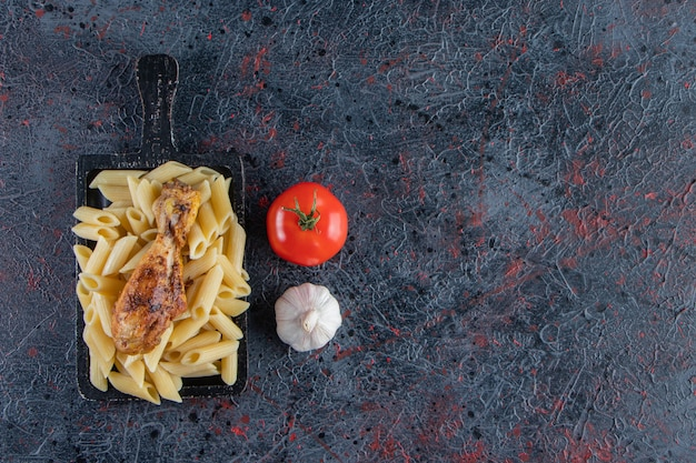 검은 커팅 보드에 맛있는 펜네 파스타와 닭 다리.