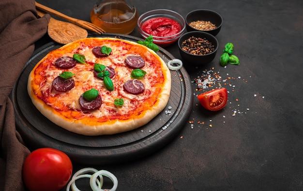 바질, 토마토, 양파, 치즈, 향신료 중 갈색 배경에 맛있는 페퍼로니 피자. 요리 배경의 개념.