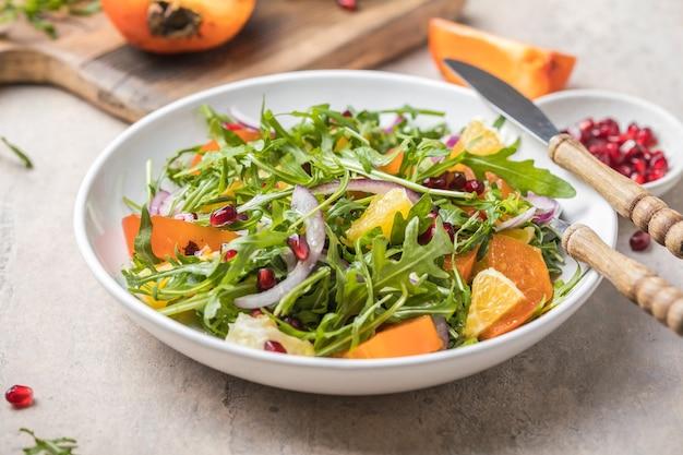 Arugula와 오렌지와 함께 맛있는 감 샐러드가 밝은 회색 테이블에 제공됩니다. 텍스트를위한 공간