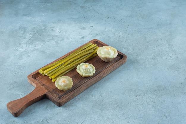 대리석 테이블에 있는 보드에 있는 맛있는 절인 미니 스쿼시와 막대기.