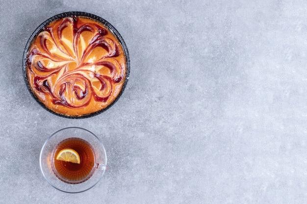 Вкусный пирог с ягодами и чашкой чая на мраморной поверхности