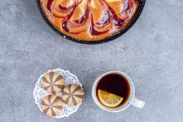 Вкусный пирог с ягодами, печеньем и чашкой чая на мраморной поверхности