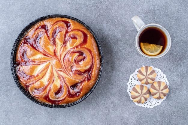 Deliziosa torta con frutti di bosco, biscotti e tazza di tè su una superficie di marmo