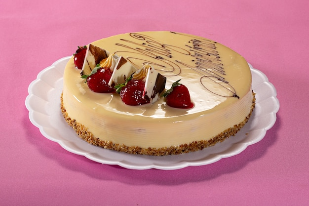 Delicious pie with peanuts and strawberry on a white plate on a pink textured background