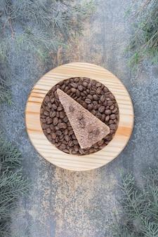 Un delizioso pezzo di torta con chicchi di caffè su tavola di legno. foto di alta qualità