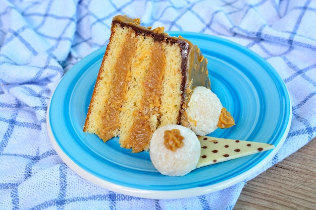 Delicious piece of dulce de leche cake with chocolate on a blue plate