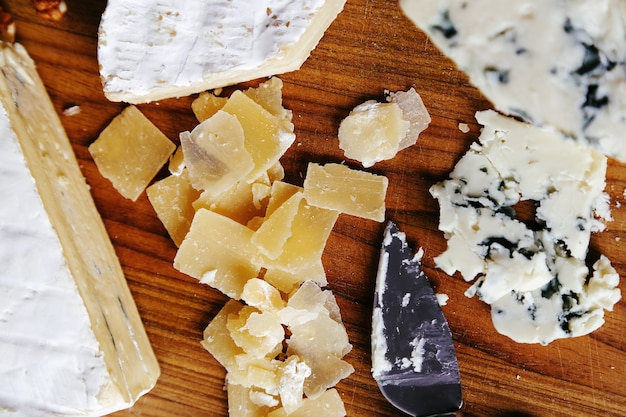 Delicious pieces of cheese wooden board