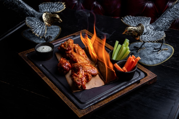 Delicious pieces of chicken wings grilled with fire flames. on restaurant black background. barbecue and grilling. restaurant dish