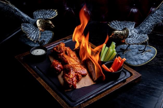Вкусные кусочки куриных крылышек на гриле с огнем пламени. барбекю и гриль. блюдо ресторана