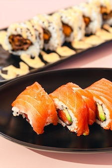 Delicious pieces of salmon and avocado sushi with sauce on a plate with pink background