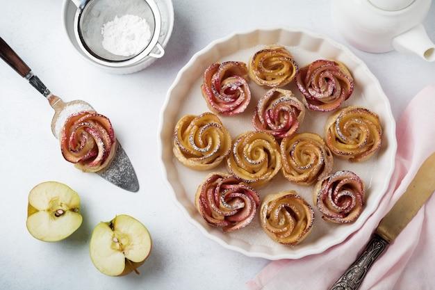 Вкусные пирожки с яблочной розой в керамической форме на светлом фоне из бетона или камня. выборочный фокус. вид сверху.