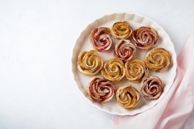 Вкусные пирожки с яблочной розой в керамической форме на легкой бетонной поверхности
