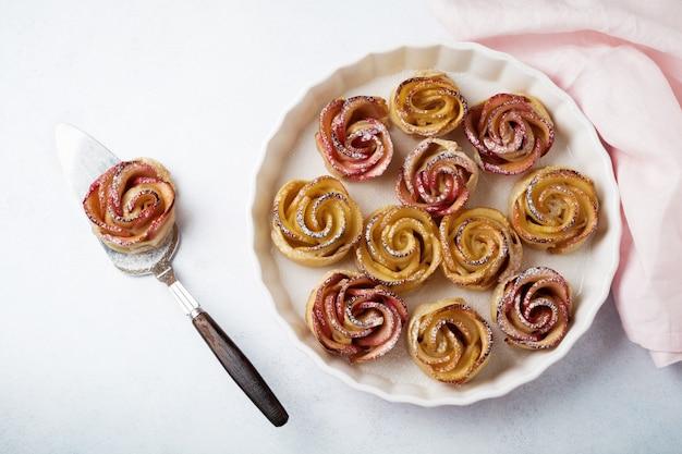 軽いコンクリートの表面にセラミックの形でリンゴのバラが付いたおいしいパイ