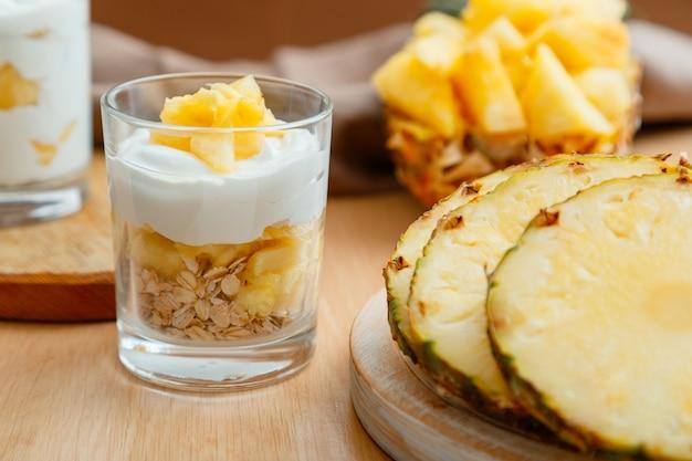 おいしいパイナップルデザート。オート麦グラノーラ、ギリシャヨーグルト、パイナップルをグラスに重ね、木製のテーブルに新鮮なジューシーなパイナップルを刻んだ朝食デザート。高品質のストックフォト。
