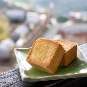 背景に美しい風景と台湾の茶屋の木製の手すりにアフタヌーンティーのためのプレートのおいしいパイナップルペストリー、クローズアップ。