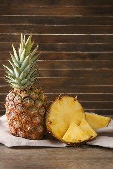 木製の壁に対してテーブルの上のスライスとおいしいパイナップル