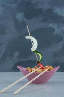 暗い背景にマカロニと箸でおいしいピンクのプレート。高品質の写真