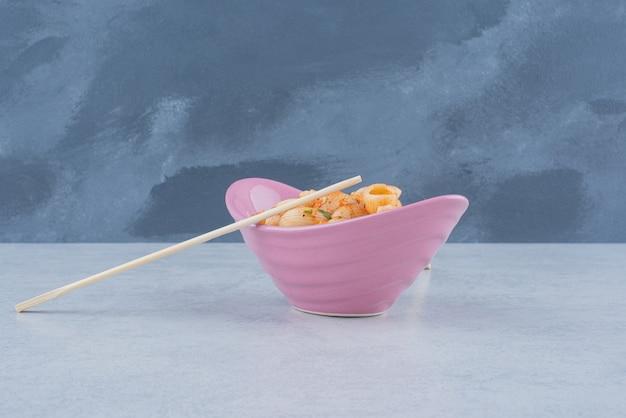 暗い表面にマカロニと箸が付いたおいしいピンクのプレート