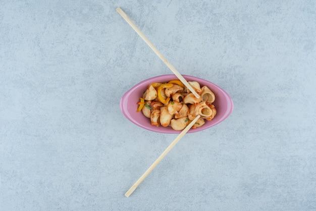 Delizioso piatto rosa con maccheroni e bacchette su sfondo scuro. foto di alta qualità