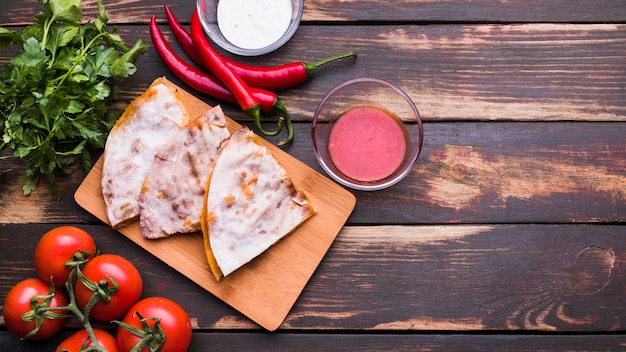 Delicious pita on chopping board near sauces among vegetables and herbs