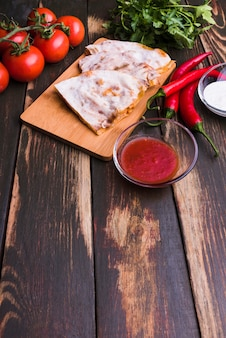 Delicious pita on chopping board near sauces among vegetables and parsley