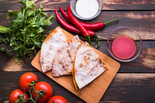 Delicious pita on cutting board near sauces among vegetables and herbs