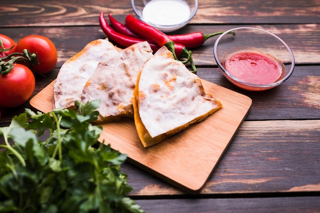 Delicious pita on cutting board near sauces among vegetables