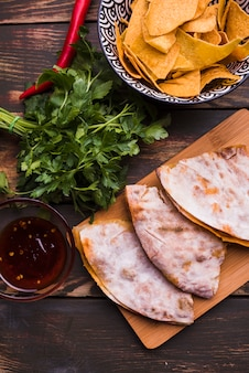 Delicious pita near herbs among nachos with sauce