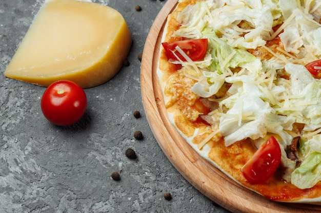 Delicious pizza caesar style with white sauce, chicken, parmesan, egg, cherry tomatoes and fresh lettuce at wooden table