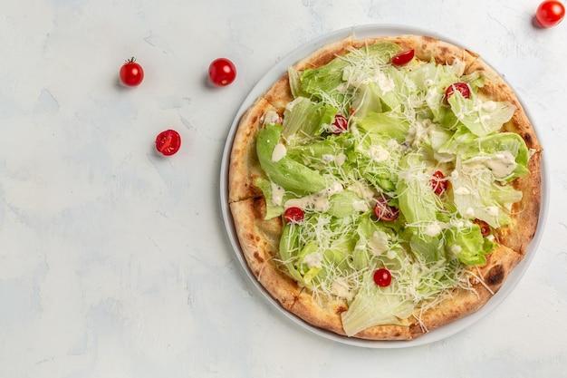 チキン、パルメザンチーズ、卵、チェリートマト、フレッシュレタスを添えたおいしいピザシーザー。バナー、メニュー、テキストのレシピの場所、上面図。