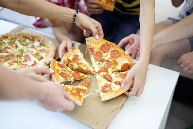 Вкусная пицца, разрезанная на кусочки на белом столе