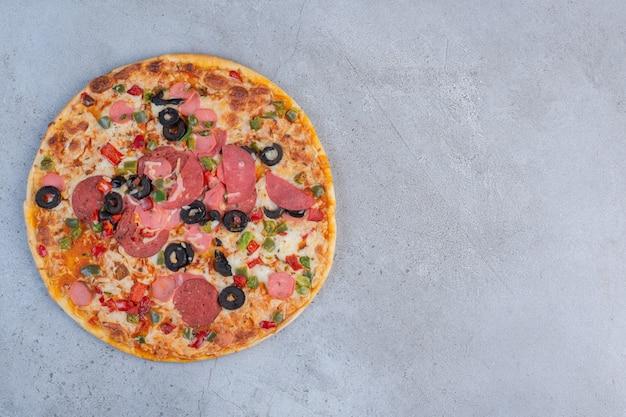 大理石の背景に表示されるおいしいピザ。