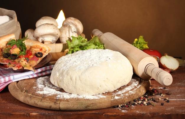 茶色の木製テーブルにおいしいピザ生地、スパイス、野菜