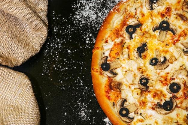 散らばった小麦粉と黒いテーブルの上のおいしいピザ新鮮なホットクローズアップ