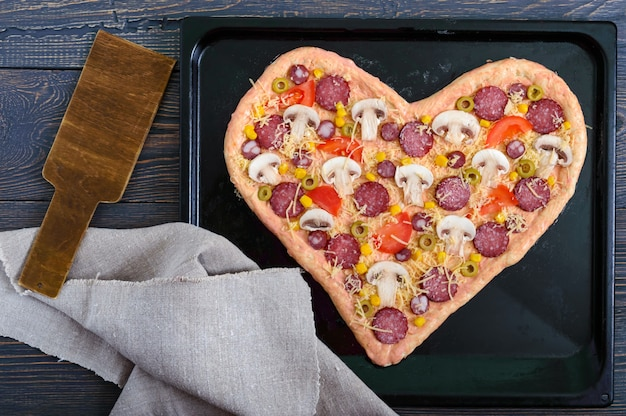 Delicious pizza in a heart shape, ready for baking. pizza with mushrooms, salami, pepperoni, olives, corn on a baking tray