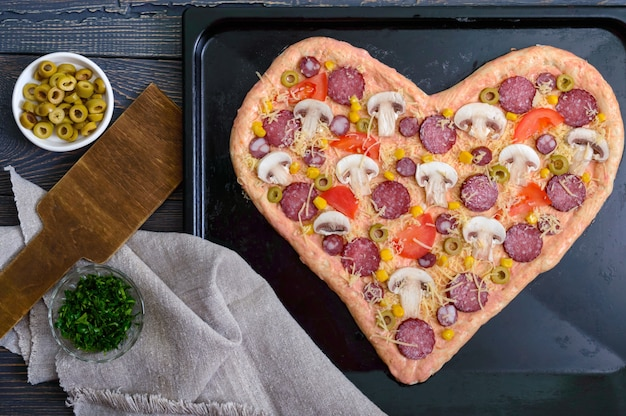 Delicious pizza in a heart shape, ready for baking