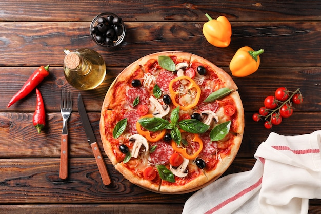 Delicious pizza and ingredients on wooden background, top view
