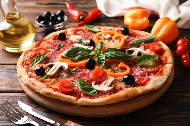 Delicious pizza and ingredients on wooden