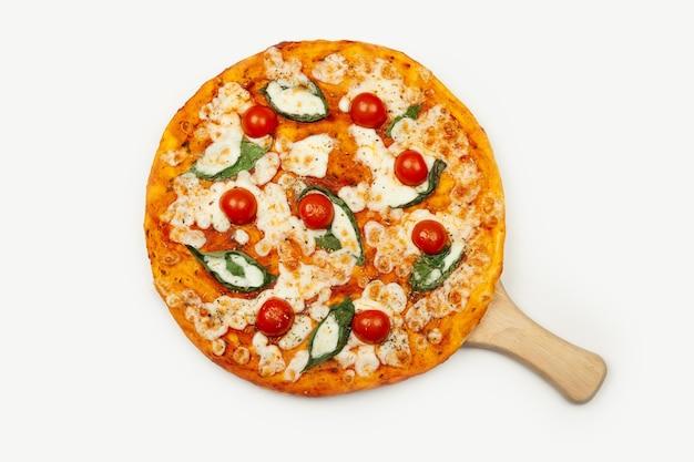 맛있는 피자 마가리타는 나무 접시 재료 소스, 바 질, 모짜렐라, 체리 토마토 흰색 절연에 재직했습니다.