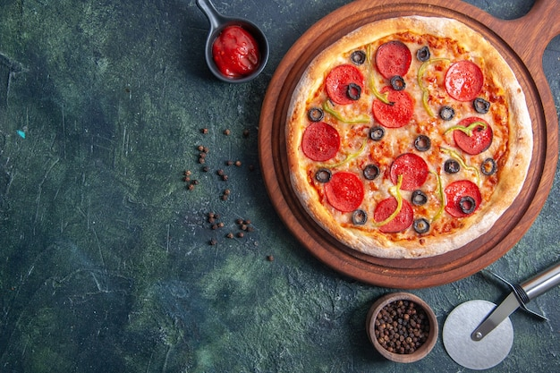 クローズ アップ ショットで孤立した暗い表面に木製のまな板とペッパー ケチャップのおいしいピザ