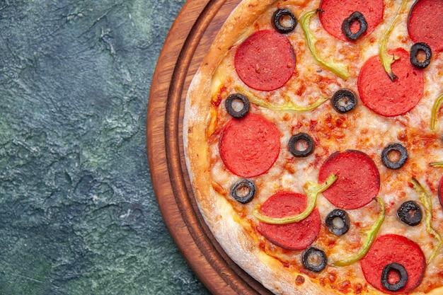 クローズ アップ ショットで空きスペースを持つ孤立した暗い表面の左側にある木製のまな板のおいしいピザ