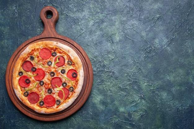 空きスペースのあるダークブルーの表面に右側の木のまな板に美味しいピザ