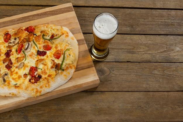 Вкусная пицца подается на подносе для пиццы с бокалом пива на деревянной доске