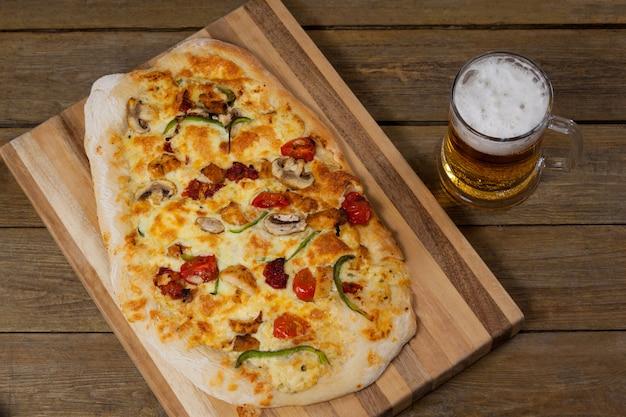 Вкусная пицца подается на подносе для пиццы с бокалом пива