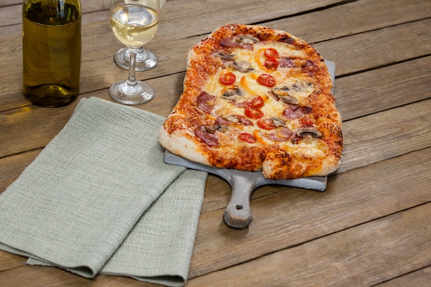 Вкусная пицца подается на подносе для пиццы с бокалами вина и бутылкой вина