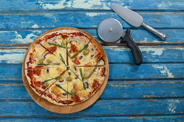 Вкусная пицца подается на подносе пиццы с резаком и ножом на деревянной доске