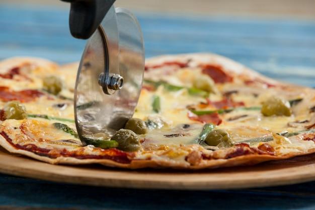 Вкусная пицца подается на подносе пиццы с резаком на пиццу