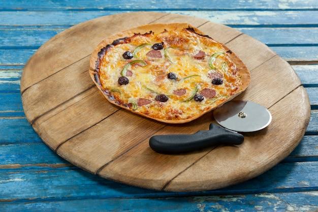Вкусная пицца подается на подносе пиццы с резаком
